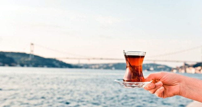 A woman holds a glass of black tea at the Bosporus, Istanbul. iStock