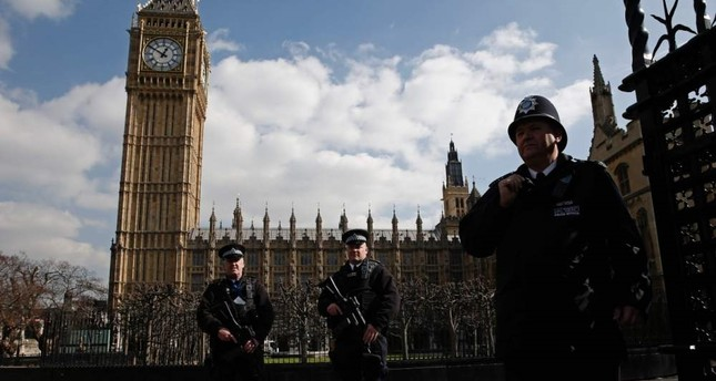 Armed British police officers stand on duty in front of the Elizabeth Tower, better known as Big Ben outside the vehicle entrance to the Houses of Parliament, London, March 22, 2016. AFP Photo