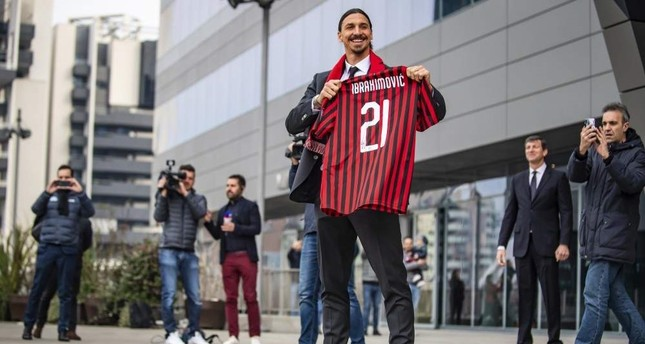 Zlatan Ibrahimovic shows an AC Milan scarf as he meets his fans outside the team headquarters, Milan, Jan. 3, 2020. AP Photo