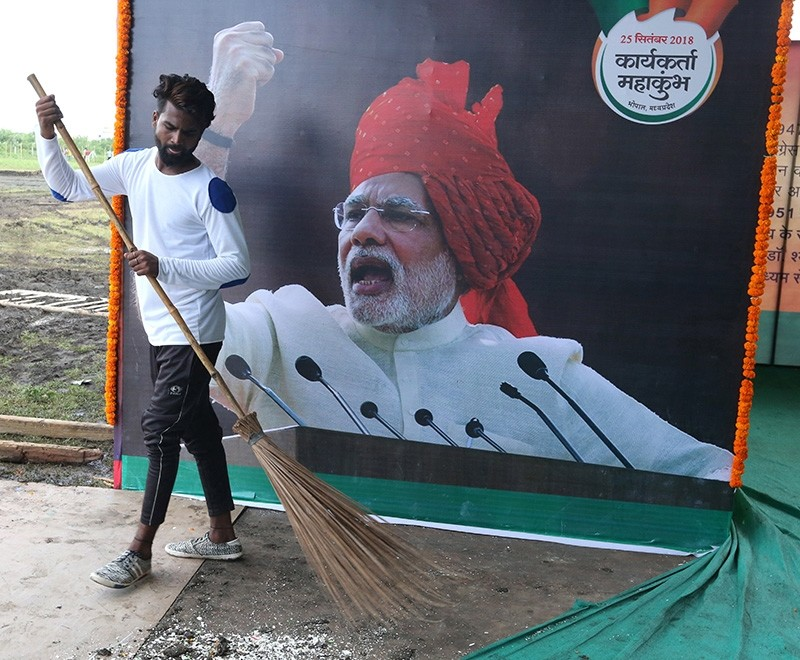 A worker sweeps near a poster of Indian Prime Minister Narendra Modi as preparations are underway at the venue for Hindu nationalist Bharatiya Janta Party's (BJP) rally in Bhopal, India, Sept. 23, 2018. (EPA Photo)