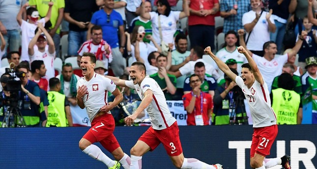 Poland's forward Arkadiusz Milik (L) is congratulated by teammates after scoring a goal during the Euro 2016 group C football match with Northern Ireland (AFP PHOTO)