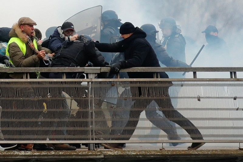 Former French boxer Christophe Dettinger, the one with the black beaine, seen during clashes with Gendarmerie as part of a demonstration by the ,yellow vests, on the passerelle Leopold-Sedar-Senghor bridge in Paris, France, January 5, 2019. (Reuters)