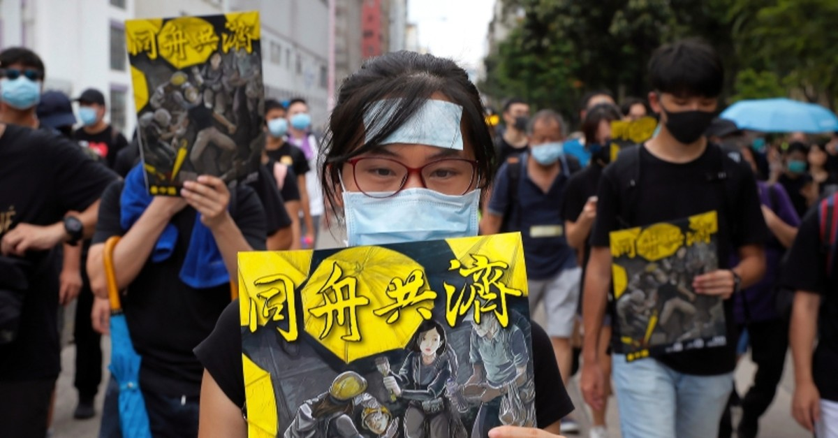 Protesters hold posters depicting protesters, medical worker and people help an injured protester bearing the words ,Together, as they take part in the anti-extradition bill protest march at Shum Shui in Hong Kong, Sunday, Aug. 11, 2019. (AP Photo)