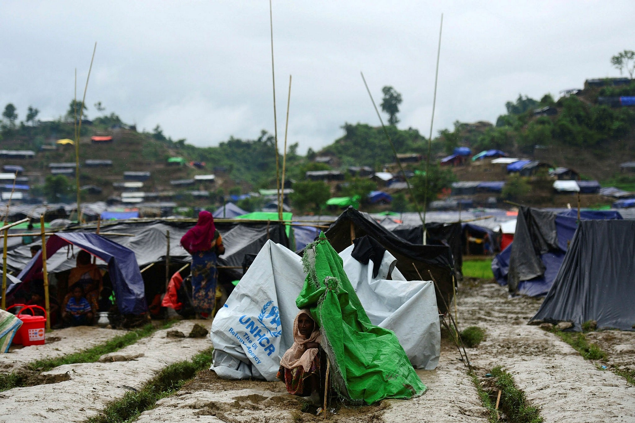 A Rohingya refugee woman sits next to a newly built makeshift shelter in a camp in Ukhia, Bangladesh on Sept.9.
