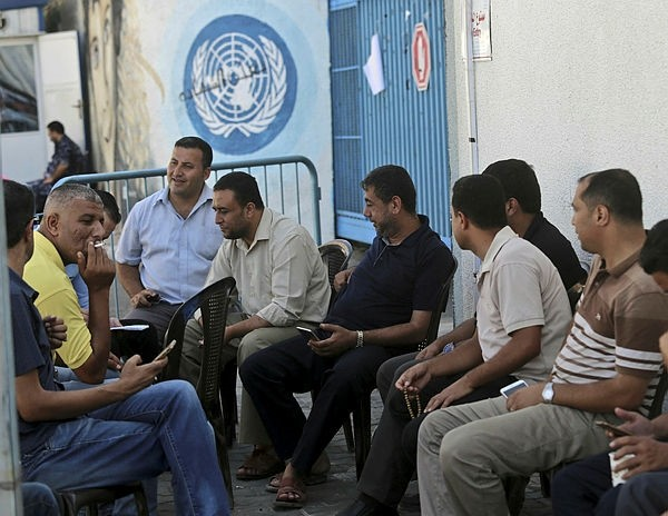 Palestinian employees of the United Nations Relief and Works Agency (UNRWA) take part in a sit in, in front of the agency's headquarters in Gaza City on October 2, 2018, to protest against job cuts announced by the UNRWA. (AFP Photo)
