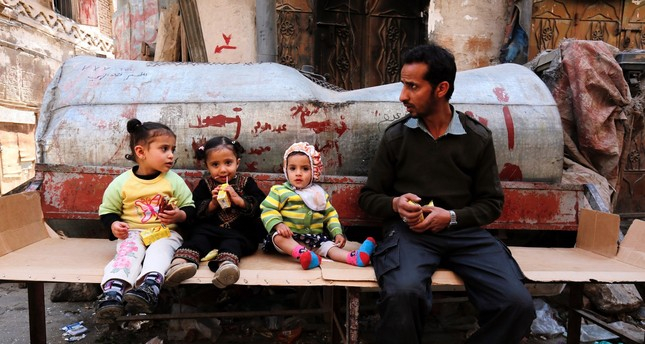A Yemeni man sits near three children in the old city of Sanaa, Jan. 26, 2017.