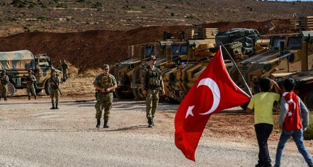 Turkish soldiers stand near armored vehicles as two boys holding Turkish flags arrive during a demonstration in support of the Turkish military's Idlib operation near the Turkish-Syrian border near Reyhanlı, Hatay, Oct. 10.