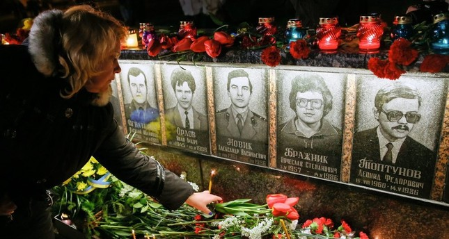 A wdman lays flowers at the memorial the 'liquidators' who died during clean up after the Chernobyl nuclear power plant disaster, during a ceremony in Slavutich, Ukraine.