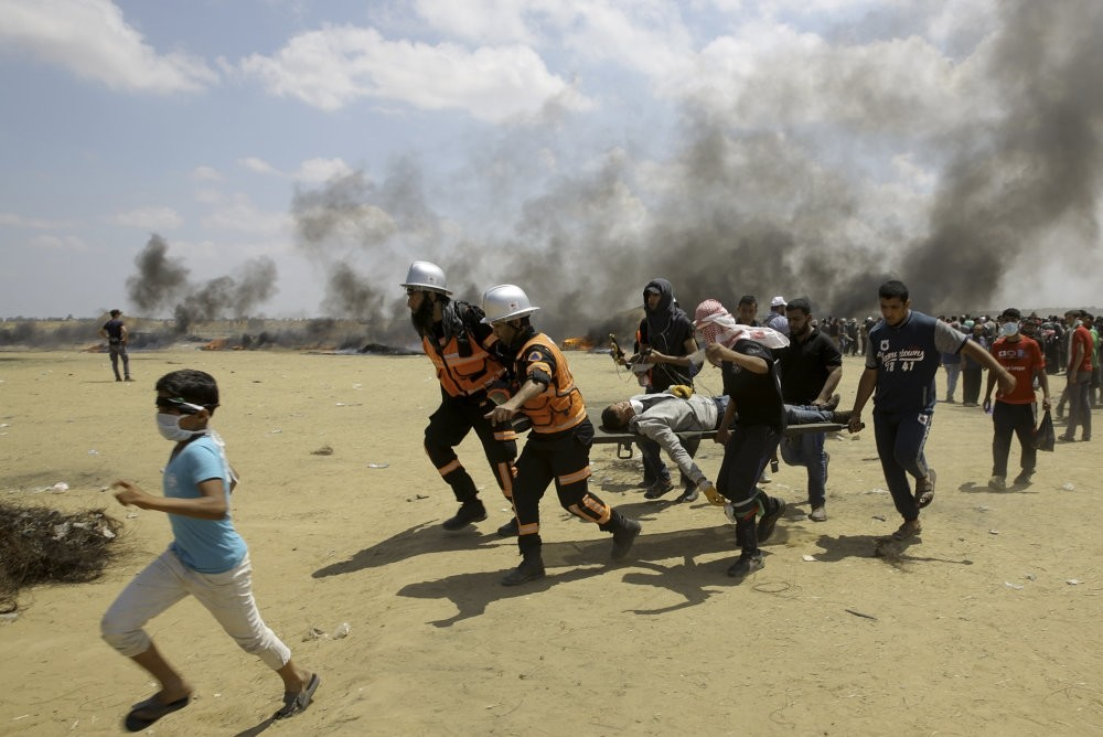 Palestinian medics and protesters evacuate a wounded young man during a protest at the Gaza Strip's border with Israel, east of Khan Younis, May 14.