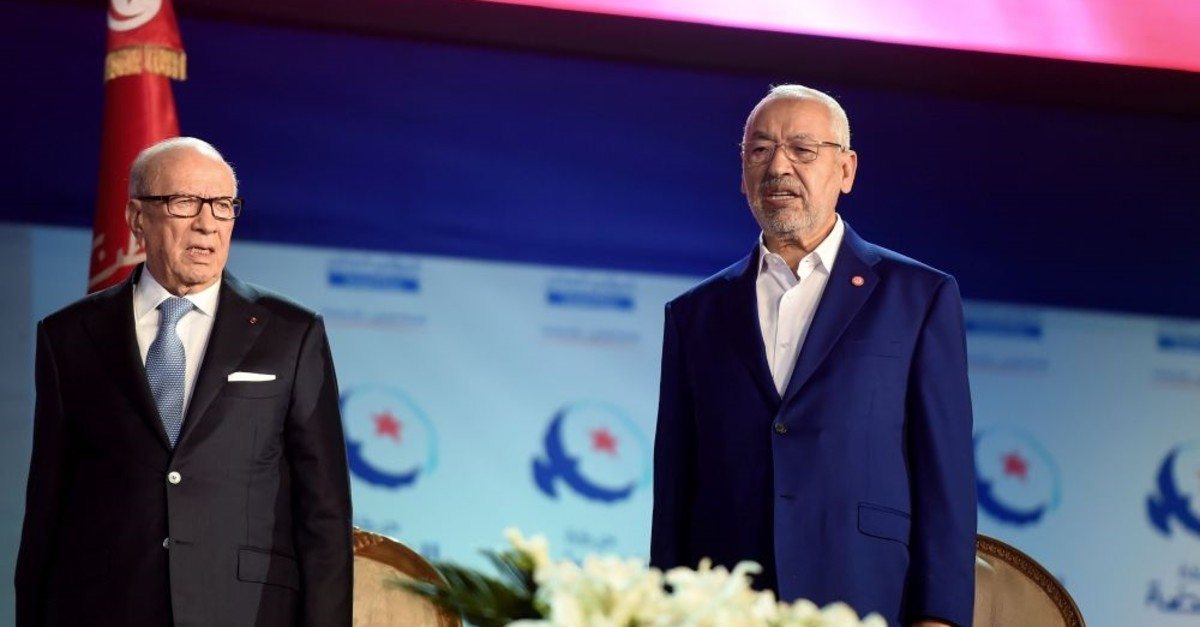 Tunisian President Beji Caid Essebsi (L) and Ennahda Party leader Rached Ghannouchi sing the Tunisian national anthem, Tunis, May 20, 2016.