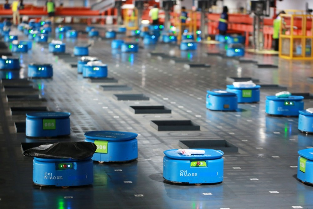 Robots operated by Alibaba's logistics unit Cainiao move packages at a new automated guided vehicles (AGV) warehouse inside the hub of the delivery company YTO Express, Hangzhou, China.