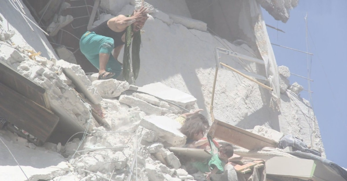 Abdulahlik Hassun calling to his nieces who were holding to each other in the ruins on the fourth floor of a building, July 26, 2019.