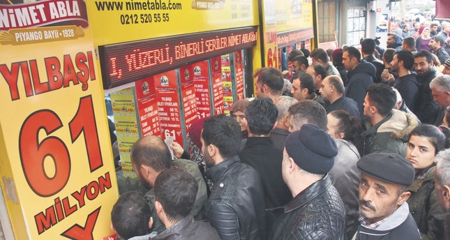 A large crowd gathers outside the 'lucky' ticket shop to buy tickets for a grand prize of TL 61 million.