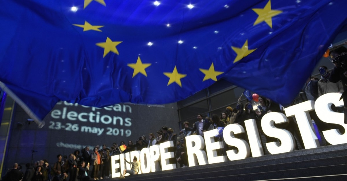 A person sits on the steps waving the Belgian flag as a group of activists hold letters forming the words u201cEurope Resistsu201d outside the European Parliament after the announcement of the results for European parliamentary elections, Brussels, May 26