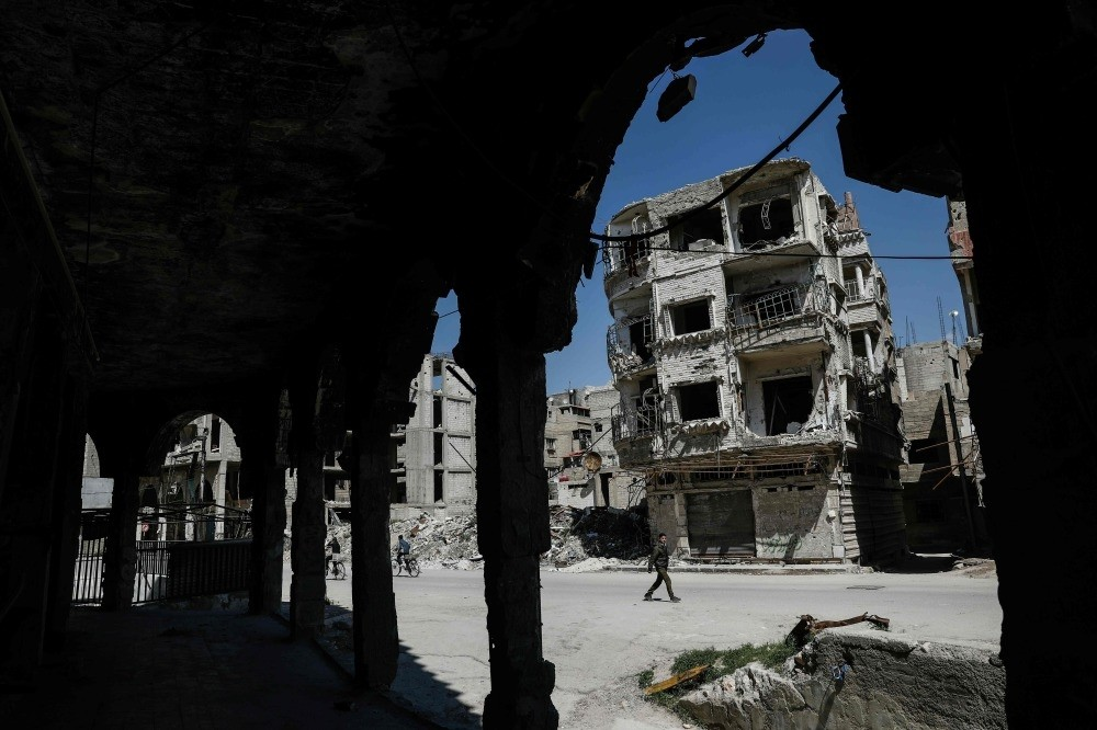 Syrians walking past damaged buildings in the moderate Syrian opposition-held town of Douma on the eastern outskirts of Damascus, April 7. ( AFP Photo)