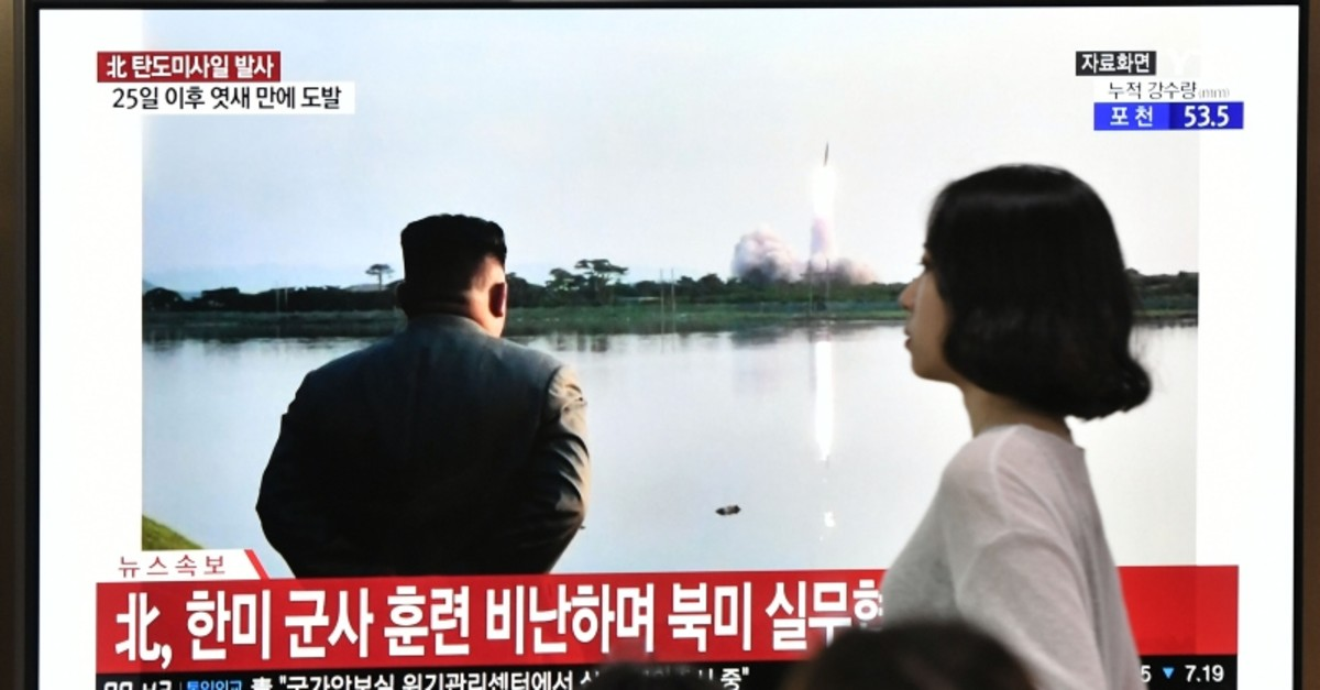 A woman walks past a television news screen showing file footage of North Korean leader Kim Jong Un watching a missile launch, at a railway station in Seoul on July 31, 2019. (AFP Photo)