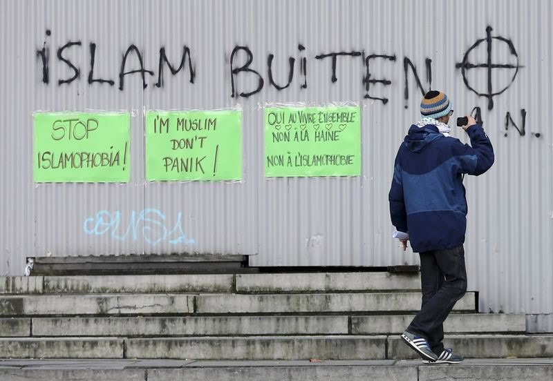 Pasted signs reading ,Stop Islamophobia, and ,Iu2019m Muslim don't panic, are seen under an anti-Islam graffiti during a protest against Islamophobia in front of the Brussels' Justice Palace October 26, 2014. (Reuters Photo)
