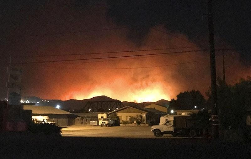 Flames from a wildfire loom up over a neighborhood in Santa Paula, Calf., Monday, Dec. 4, 2017. (Megan Diskin/The Ventura County Star via AP)