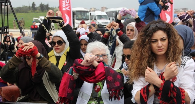 Activists shackled in scarves symbolizing handcuffs to raise awareness of female prisoners.