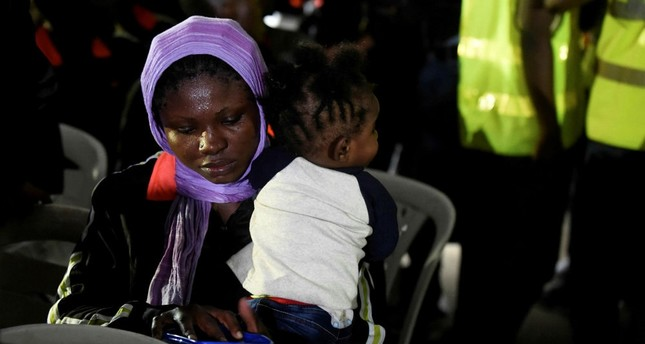 A female migrant tries to feed a child after leaving a chartered aircraft that brought migrants home from Libya, Lagos, Dec. 5, 2017.