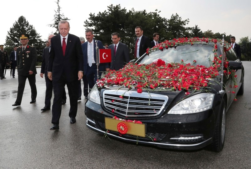 Erdoğan walks out of his car decorated with flowers thrown by supporters on his way the mausoleum of the nation's founding father Mustafa Kemal Atatürk, in Ankara.