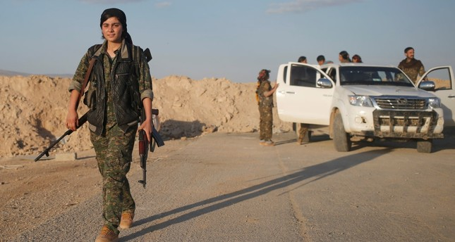 A female member of the Sinjar Resistance Units (YBS), a militia affiliated with the PKK, carrying a sniper and an AK-47 rifle in the village of Umm al-Dhiban, Northern Iraq.