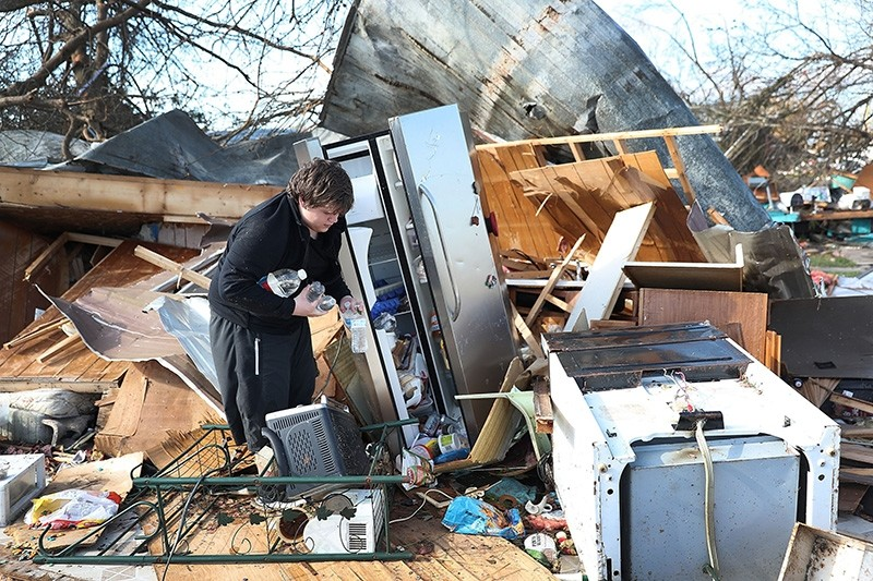 Gavin Conklin, 17, gathers water bottles from a neighbor's refrigerator after Hurricane Michael destroyed the home on October 11, 2018 in Panama City, Florida. (AFP Photo)