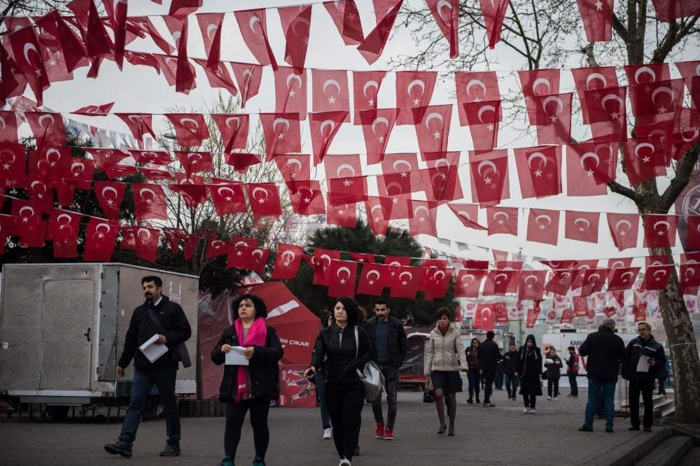 People walking under Turkish flags in an Istanbul street two days ahead of the referendum on whether the current post-coup constitution should be changed or not. (AFP Photo)