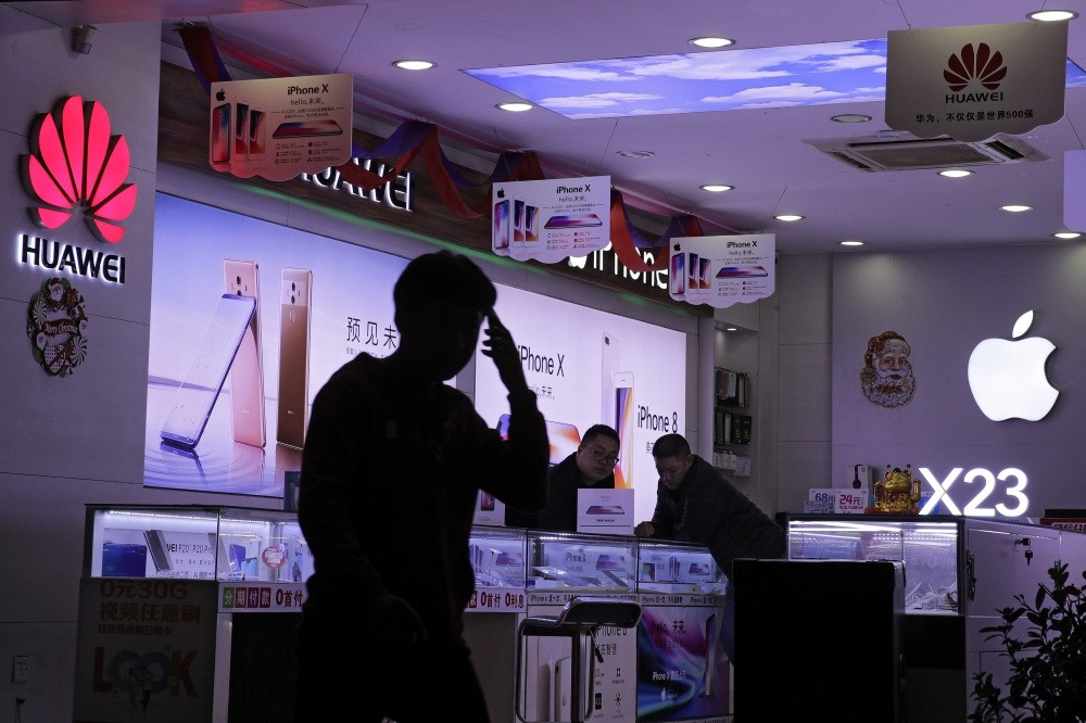 A man walks by a worker attending to a customer at a mobile phone retail shop selling Huawei and Apple smartphones in Shenzhen in south China's Guangdong province yesterday.