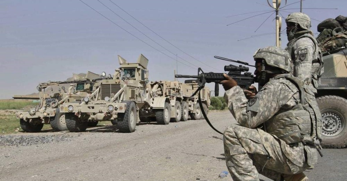A U.S. soldier looks at an approaching man through the sights of his assault rifle as soldiers provide security during investigations at a site of a suicide attack in Kandahar, Afghanistan, May 20, 2010. (AP Photo)