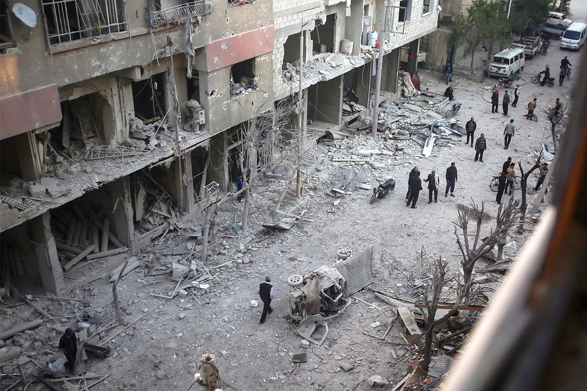 People inspecting damaged buildings after an airstrike by the Assad regime in opposition-held Douma, Syria, April 7. (EPA Photo)