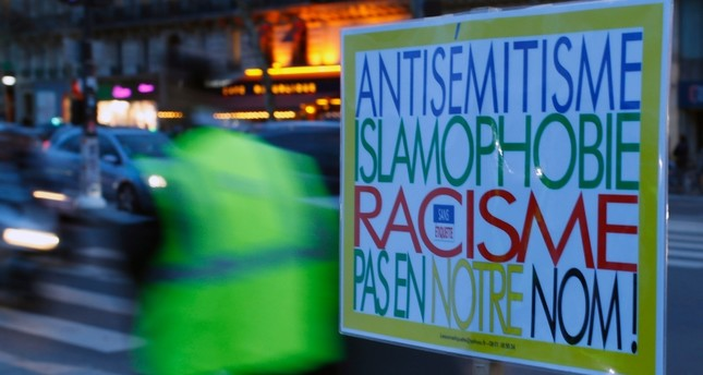 A poster reading Anti-Semitism, Islamophobia, Racism, Not in Our Name during a gathering decrying anti-Semitism at Place de la Republique in Paris, Monday, Feb. 18, 2019, amid an upsurge in anti-Semitism in France. (AP Photo)