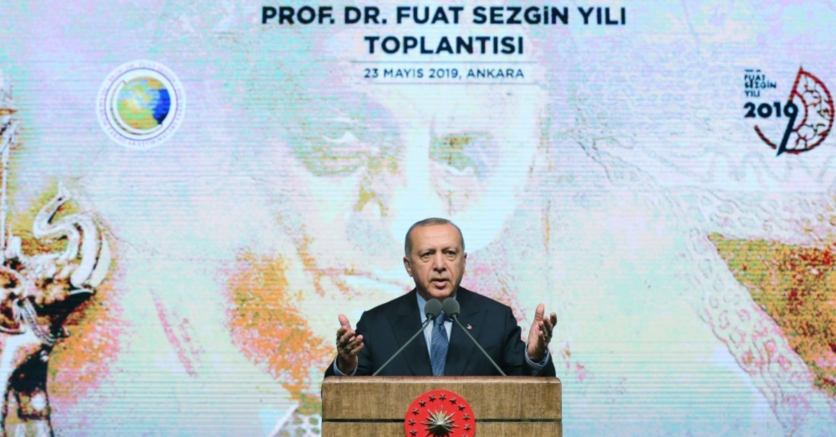 President Erdou011fan speaks in front of a poster of Sezgin at the presidential complex, May 23, 2019.