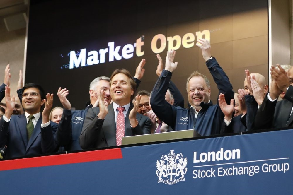 Andy Palmer (C-R), CEO of Luxury British sports car manufacturer Aston Martin applauds in celebration as the company was floated on the London Stock Exchange on Oct. 3.