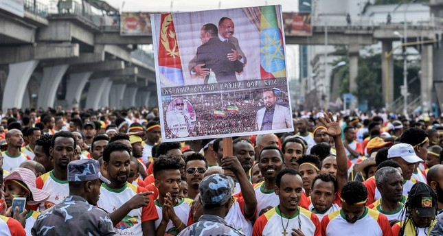 Competitors hold a banner with images of leaders as they gather to run the first Ethiopia-Eritrea Peace and Reconciliation Run 10km at Meskel Square in Addis Ababa on Nov. 11, 2018. AFP Photo