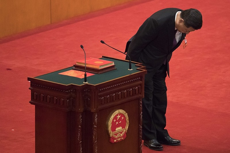 Xi Jinping bows after taking the oath of office after being formally re-elected to a second term as President during a plenary session of China's National People's Congress at the Great Hall of the People in Beijing, March 17, 2018. (AP Photo)