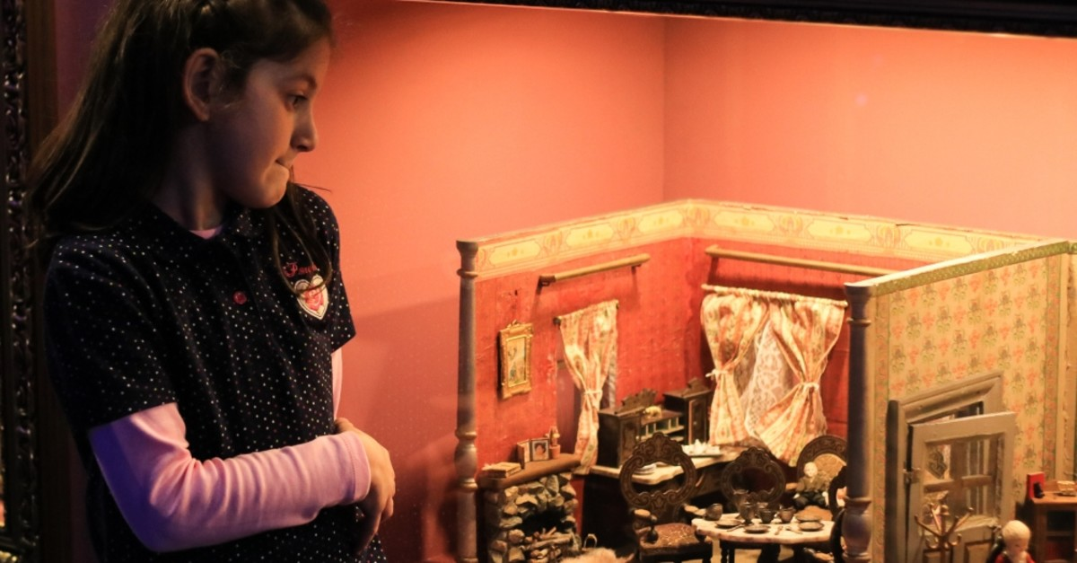 A girl examines an old doll house displayed at the museum.