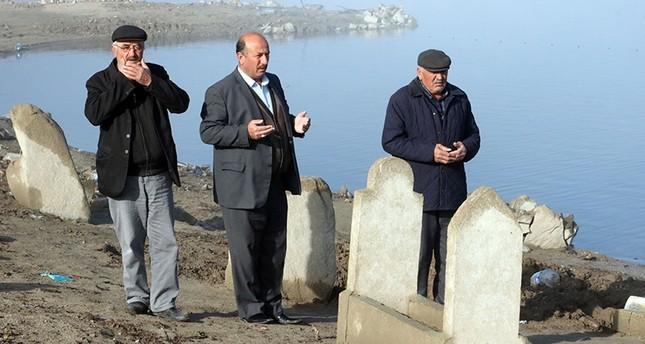 القرويون يقرؤون الفاتحة على أحد القبور التي كشف عنها انحسار مياه السد (İHA)
