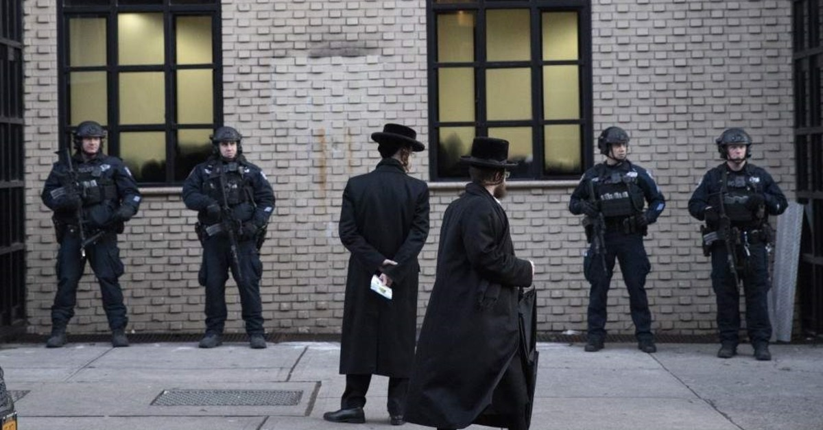 Orthodox Jewish men pass New York City police guarding a Brooklyn synagogue, New York, Dec. 11, 2019. (AP Photo)