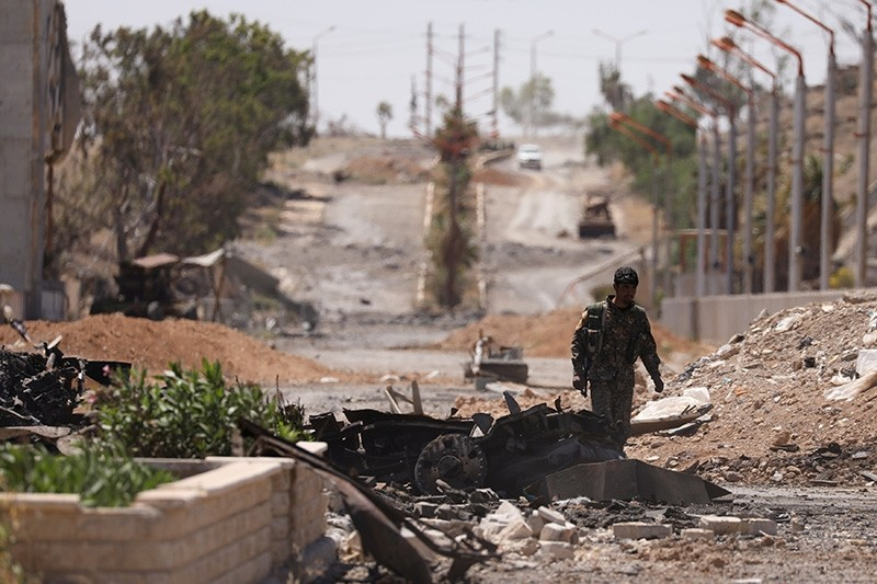A Syrian Democratic Forces (SDF) fighter walks through a damaged street in the town of Tabqa, after SDF captured it from Daesh militants this week, in Raqqa, Syria, May 12, 2017. (Reuters Photo)