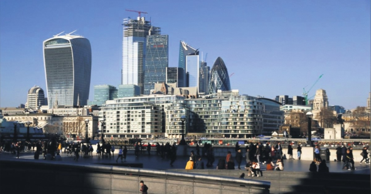 The financial district can be seen as a person runs in the sunshine on London's south bank, Britain, Feb. 23, 2019.