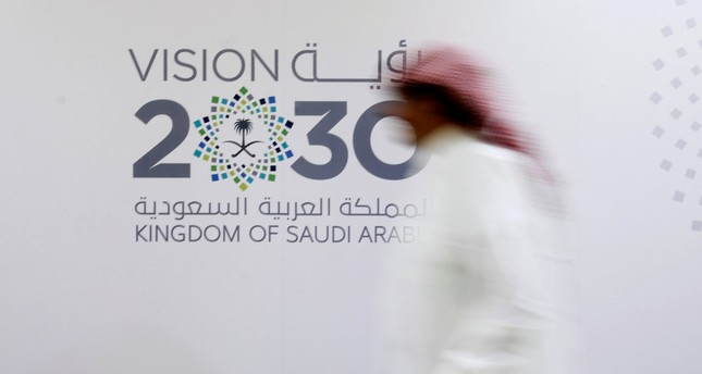 A Saudi man walks past the Vision 2030 logo after a news conference in Jeddah, Saudi Arabia.