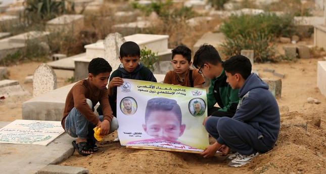 Friends of 15-year-old Palestinian Mohammed Ibrahim Ayoub, who was shot and killed by Israeli security forces during clashes along the Israel-Gaza border, hold up a poster of his portrait by his grave in a cemetery in Gaza. (AFP Photo)