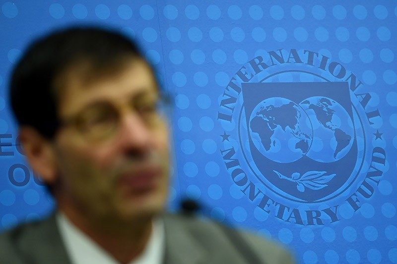 International Monetary Fund (IMF) logo is seen in the background as chief economist Maurice Obstfeld (L) answers questions from members of the media in Kuala Lumpur on July 24, 2017. (AFP Photo)