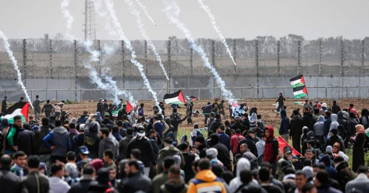 Tear gas canisters fall among Palestinian protesters during a demonstration near the border with Israel, Gaza City, March 30, 2019. (AFP Photo)