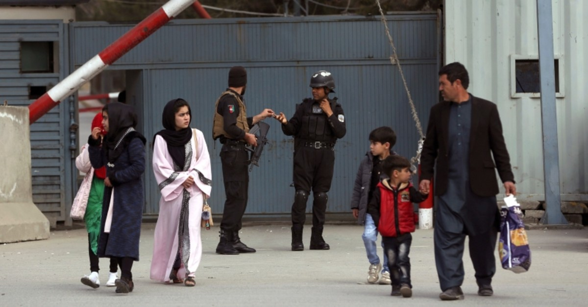 Afghan family walk near the site of an explosion in Kabul, Afghanistan, Thursday, March 21, 2019. (AP Photo)