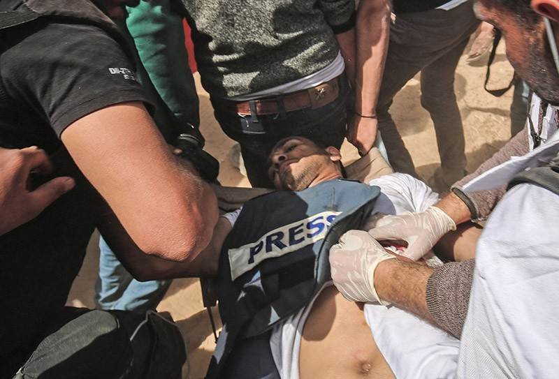 Demonstrators assist Palestinian journalist Yasser Murtaja, shot by Israeli soldiers during protests near the border with Israel. (AFP Photo)