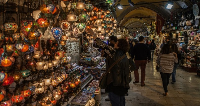 People examining various goods sold at Istanbul's Grand Bazaar which dates back to the 15th century.