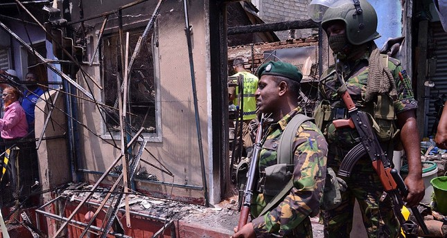 Sri Lanka's security forces stand near a vandalized building in Digana, a suburb of Kandy, Sri Lanka, March 6, 2018. (AP Photo)