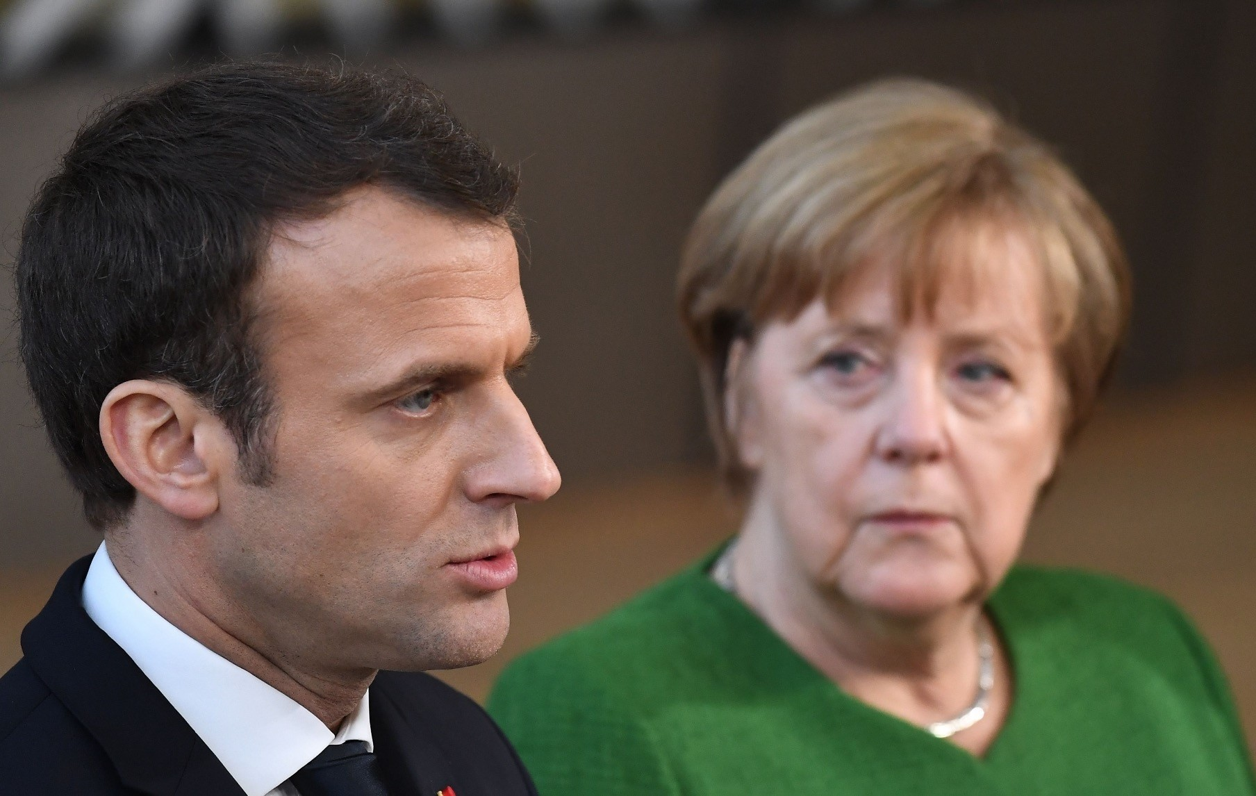France President Macron (L) speaks to journalists next to German Chancellor Angela Merkel as they arrive for an informal meeting of the 27 EU heads of state and government at European Council headquarters, Brussels,  Feb. 23.